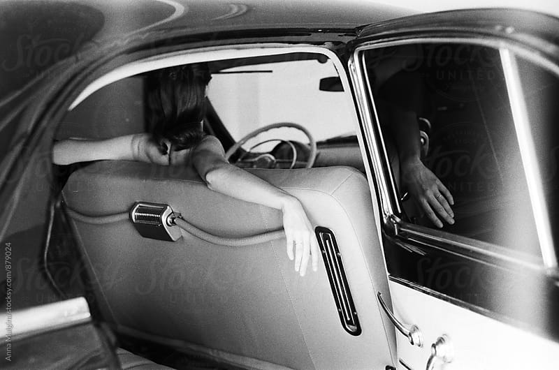 A black and white back portrait of a young woman seating in the retro car by Anna Malgina for Stocksy United