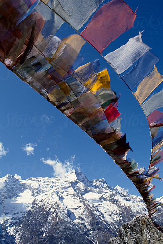 Prayer flag fluttering ni the Himalayas. Nepal by Hugh Sitton for Stocksy United