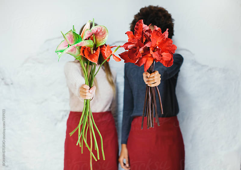Women covering their faces with a bouquet of flowers on white. by BONNINSTUDIO for Stocksy United