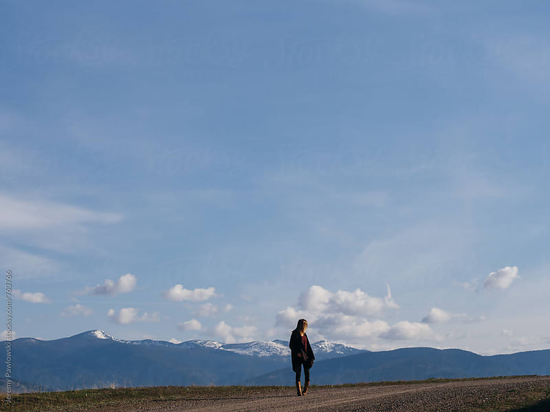 Girl walking on Montana dirt road with mountains in background by Jeremy Pawlowski for Stocksy United