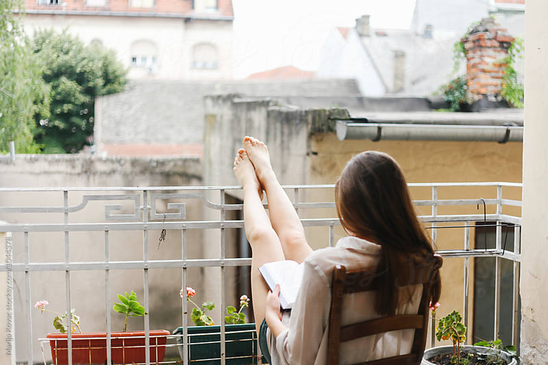 Caucasian woman reading a book on her terrace, from behind by Marija Kovac for Stocksy United