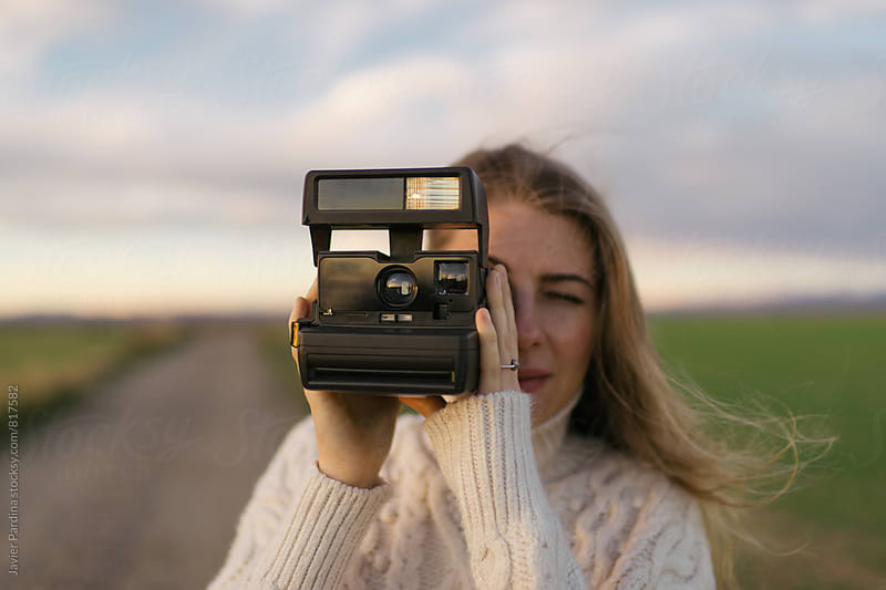 Woman taking photo with instant camera by Javier Pardina for Stocksy United