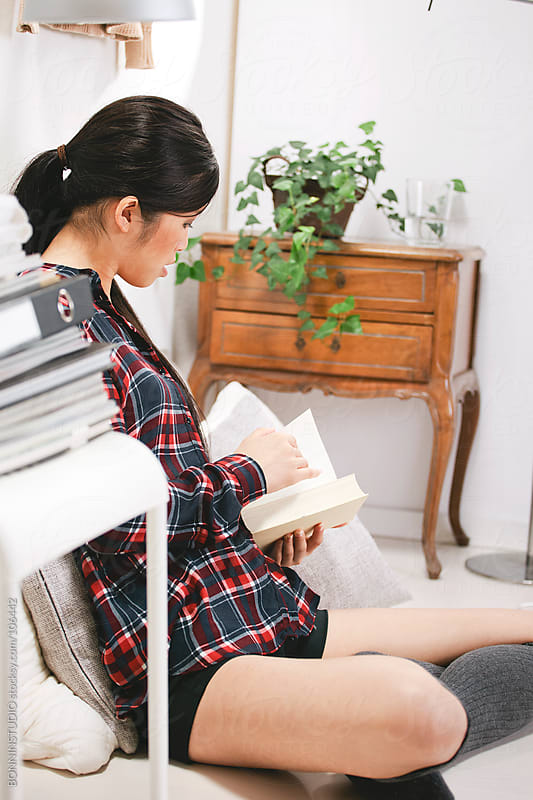 Casual asian woman reading a book in home.  by BONNINSTUDIO for Stocksy United