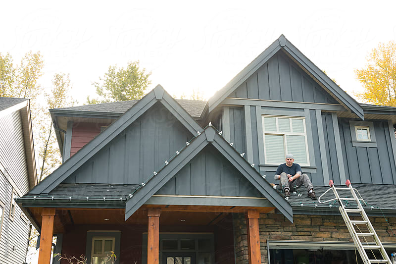 Man Installing Christmas Lights by Ronnie Comeau for Stocksy United