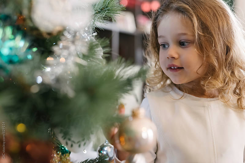 Cute young girl decorating a Christmas Tree by WAVE for Stocksy United