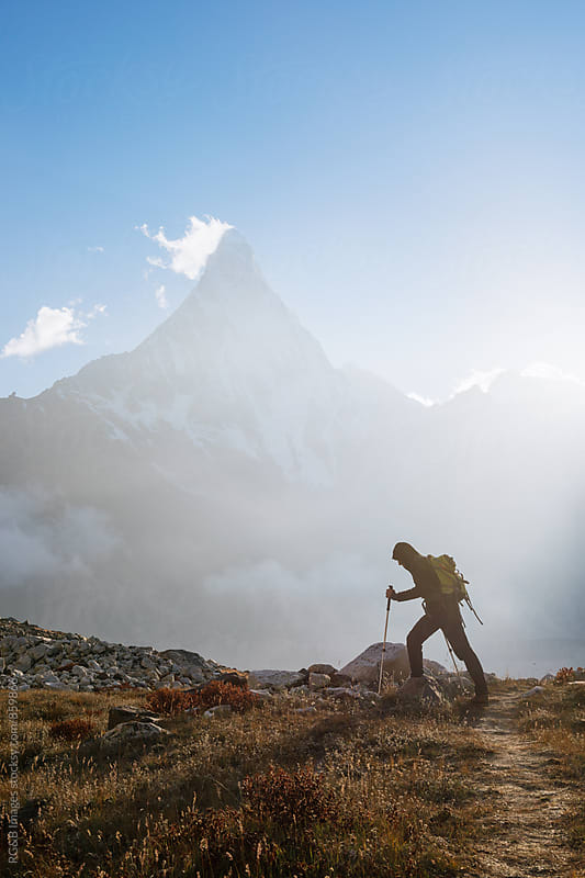 Hiker with backpack and trekking poles heading to the mountain by RG&B Images for Stocksy United