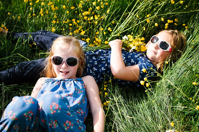 Female friends in a wildflower meadow in sunglasses by Helen Rushbrook for Stocksy United