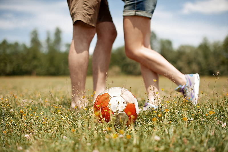 Young man and girl are playing soccer by Svetlana Shchemeleva for Stocksy United