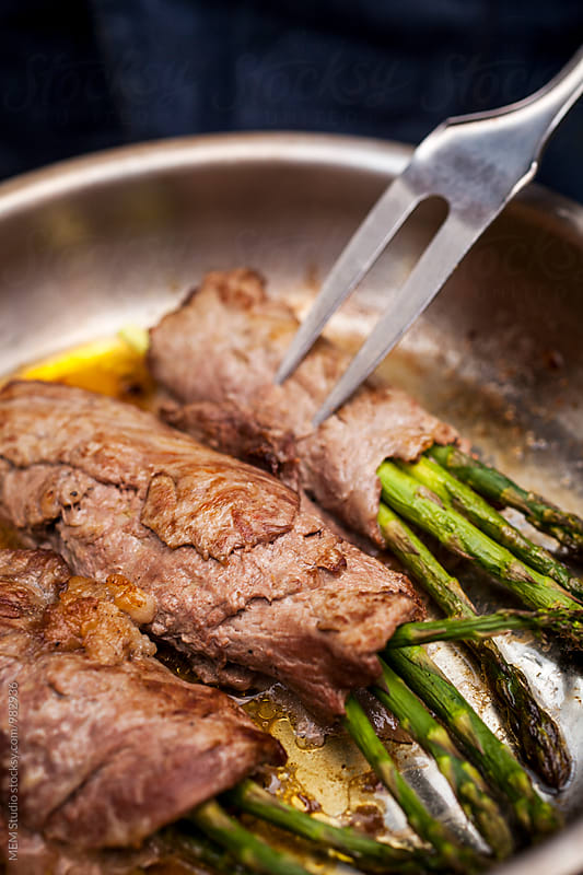 Pork with asparagus in a pan by MEM Studio for Stocksy United