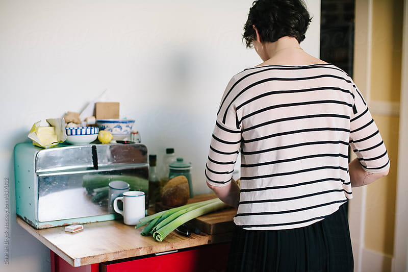 Prepping lunch in a sunny kitchen. by Cherish Bryck for Stocksy United