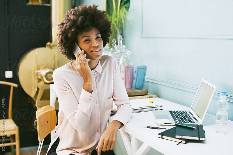African american woman talking on phone sitting in office. by BONNINSTUDIO for Stocksy United