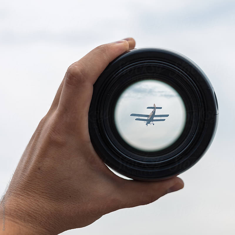 View through spyglass lens to the small airplane in the sky by Ilya for Stocksy United
