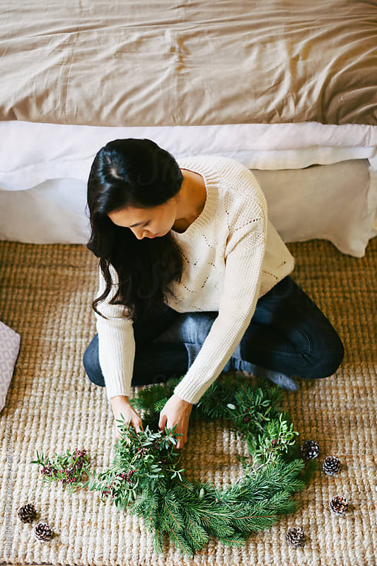 Young asian woman making a Christmas wreath at home. by BONNINSTUDIO for Stocksy United