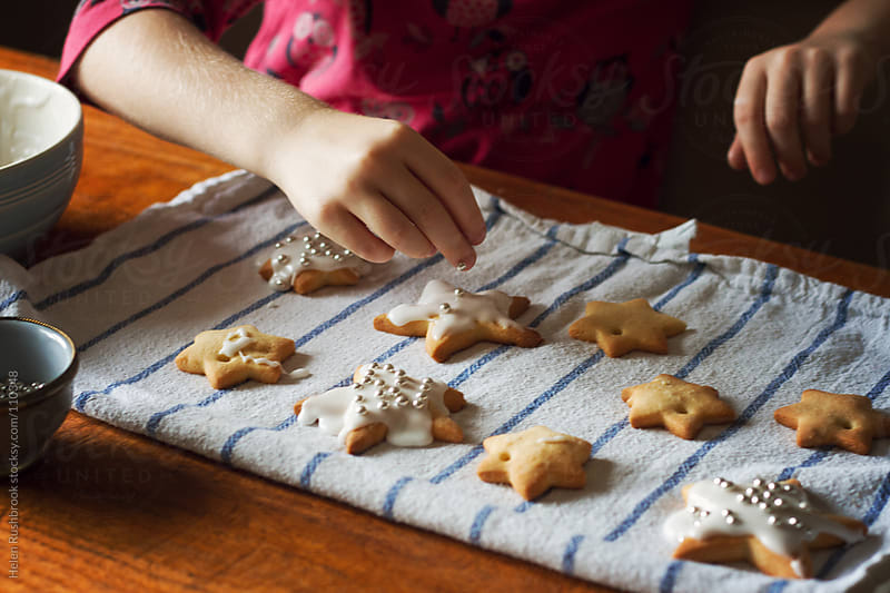 A little girl decorating star-shaped cookies by Helen Rushbrook for Stocksy United