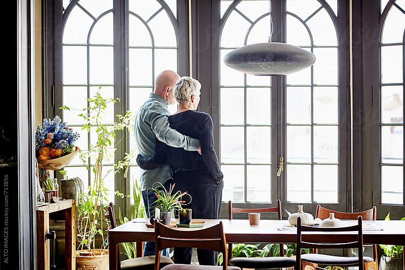 Loving Senior Couple Standing Arms Around At Home by ALTO IMAGES for Stocksy United