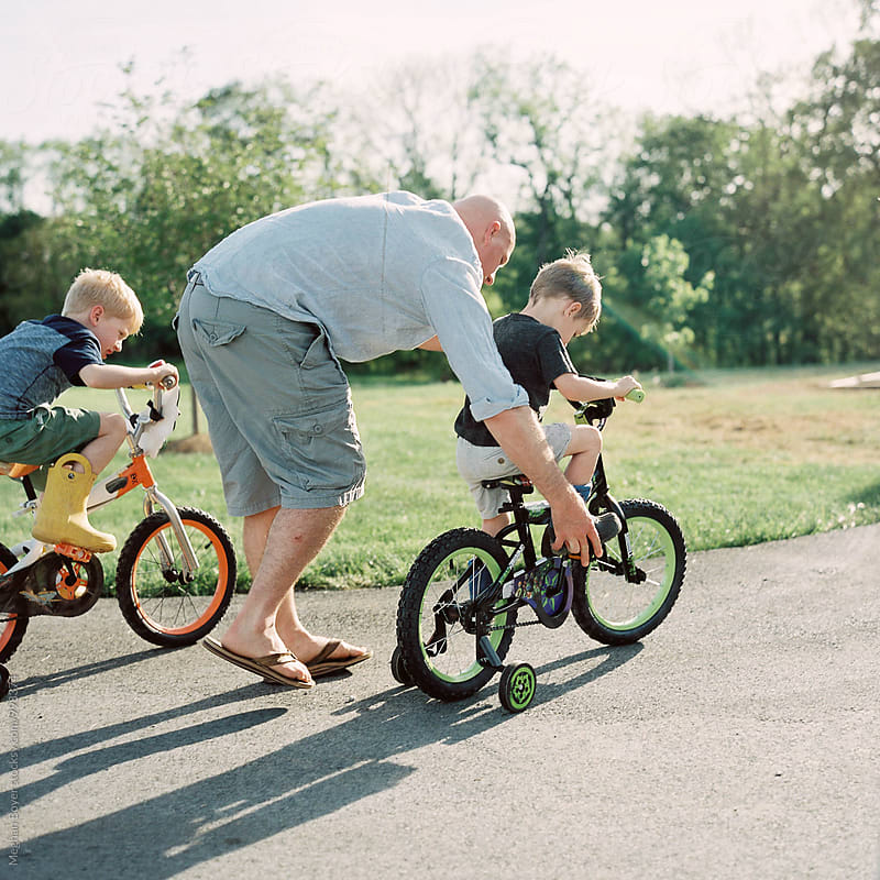 Father Teaching sons how to ride a bike by Meghan Boyer for Stocksy United
