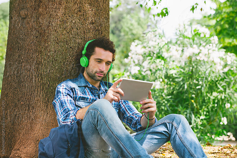 Young handsome man listenning music with digital tablet under a big tree. by BONNINSTUDIO for Stocksy United