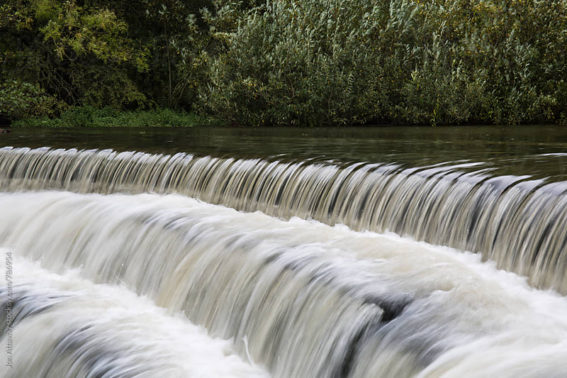 White water rushing over a weir by Jon Attaway for Stocksy United