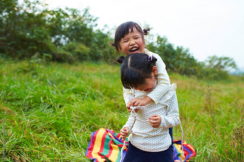 two lovely little asian girl having fun outdoor in the nature by cuiyan Liu for Stocksy United