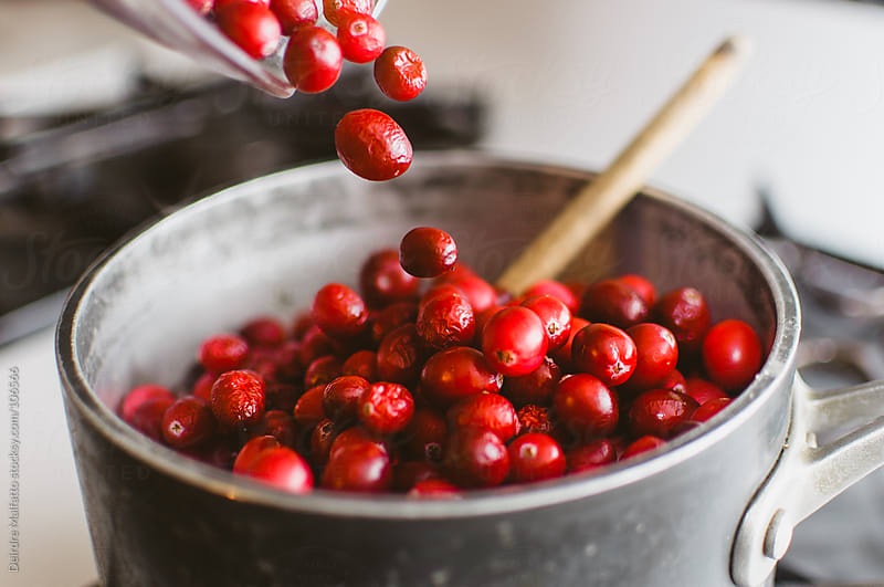 fresh cranberries being poured into pot on stove by Deirdre Malfatto for Stocksy United
