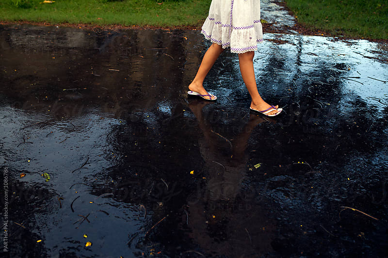 A teenage girl walking through a wet road caused by rain water by PARTHA PAL for Stocksy United