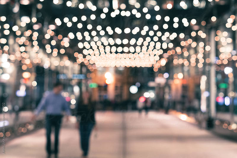 Blurred couple walking under holiday lights by James Jackson for Stocksy United