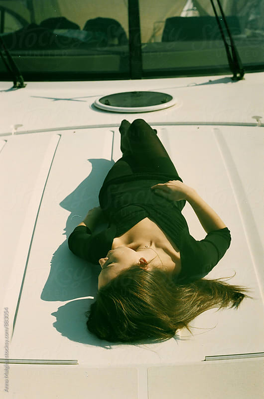 A film portrait of young beautiful woman lying on the yacht by Anna Malgina for Stocksy United