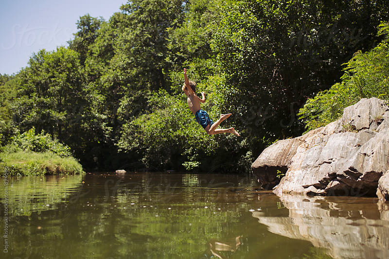 Playful boy jumping in river. by Dejan Ristovski for Stocksy United