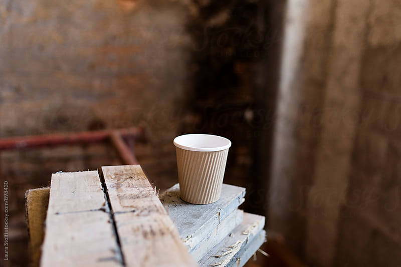 Paper mug on wooden board on working site by Laura Stolfi for Stocksy United