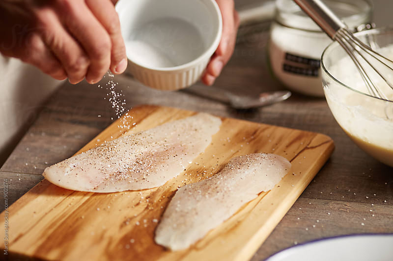 Man salting raw fish slices by Martí Sans for Stocksy United