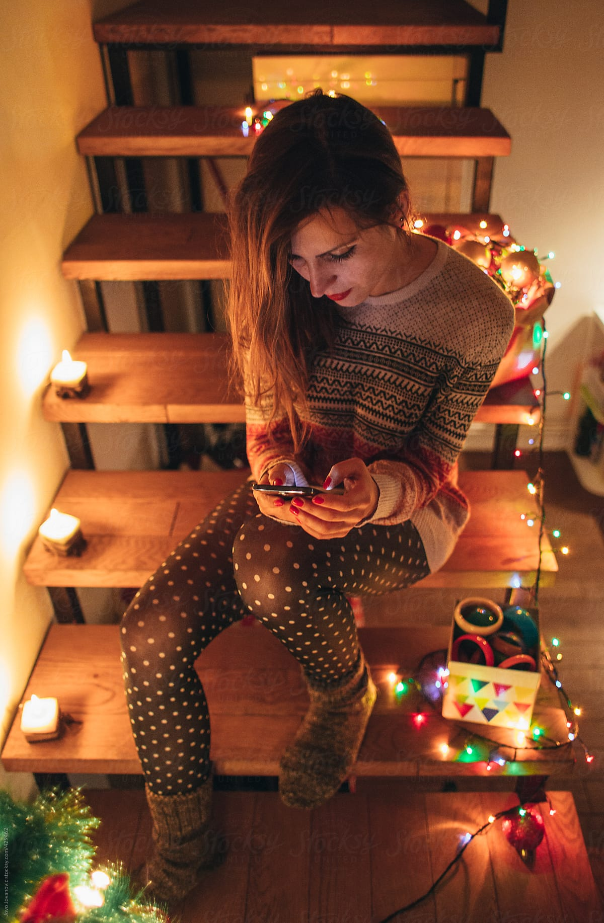 Alone On Christmas.Woman Sitting Alone On Christmas Night And Using Her Phone