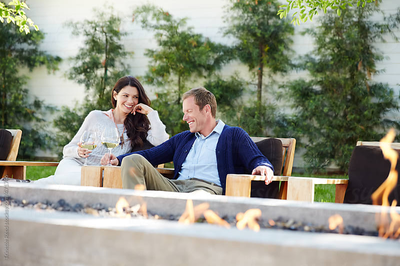 Couple relaxing at outdoor lounge fire pit with wine.  by Trinette Reed for Stocksy United