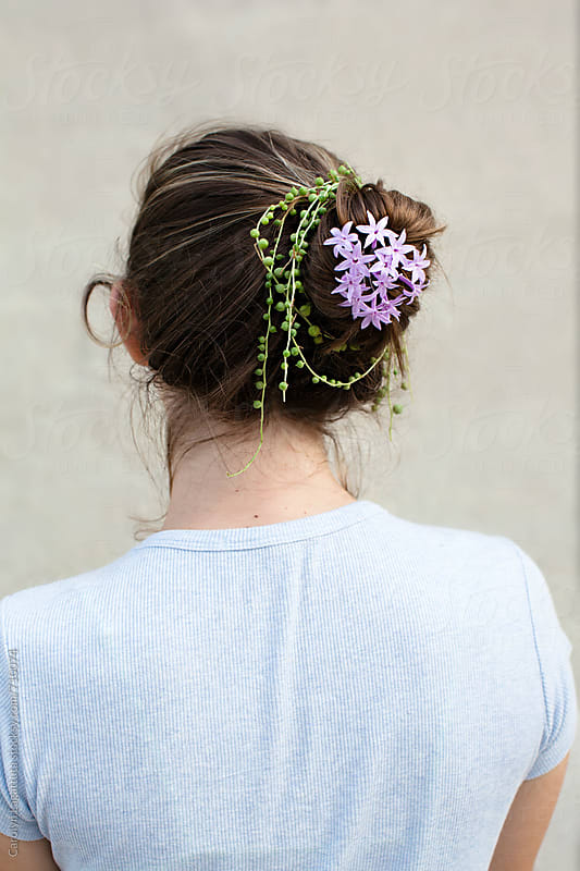 Back view of a teenage girl with a bun in her hair decorated with succulents and flowers by Carolyn Lagattuta for Stocksy United