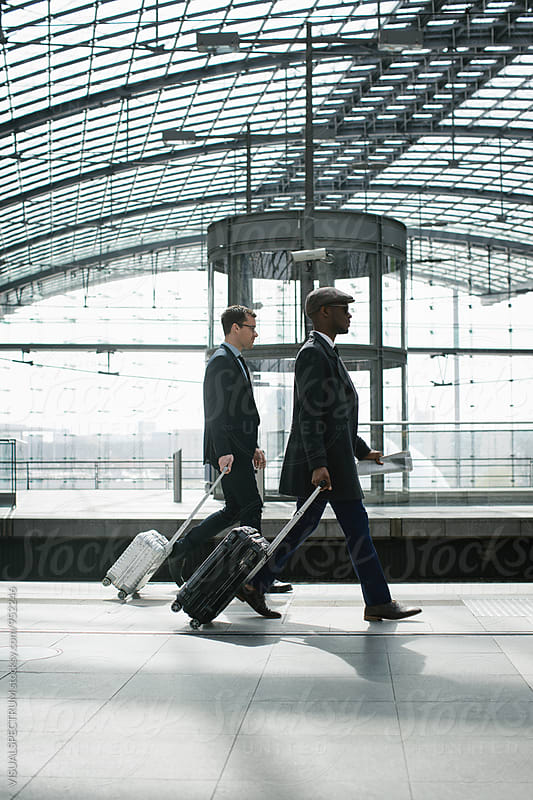 Two Young Business Travelers Walking With Carry On Suitcases in Modern Train Station by Julien L. Balmer for Stocksy United
