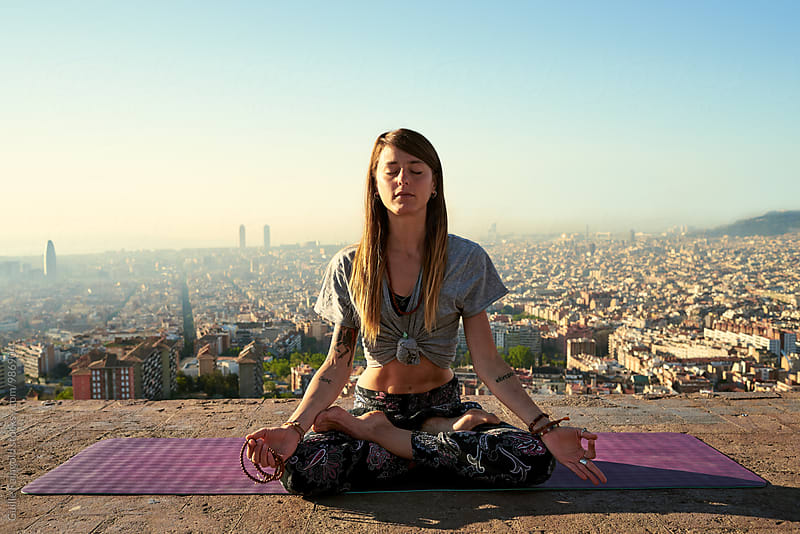 Young meditating woman in lotus position against of scenic cityscape of Barcelona by Guille Faingold for Stocksy United