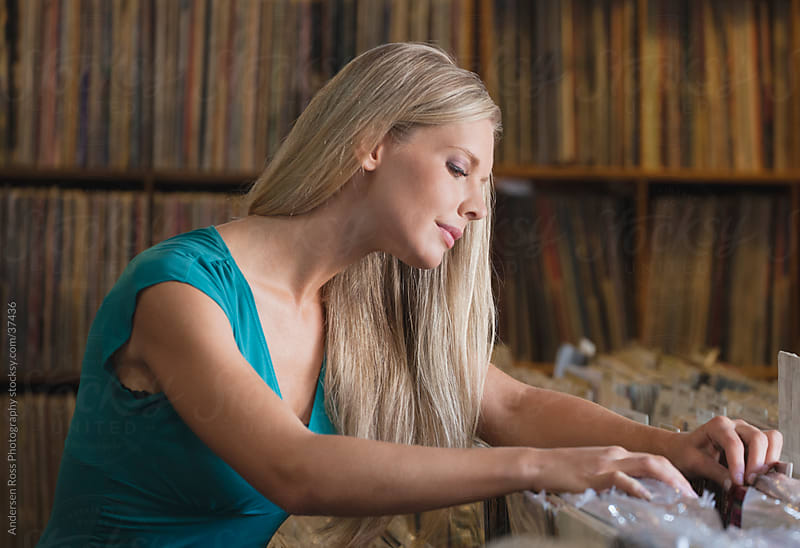 Woman browsing through records in record shop by Andersen Ross Photography for Stocksy United