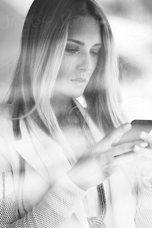 Young businesswoman working with smartphone. Black and white photo. by BONNINSTUDIO for Stocksy United