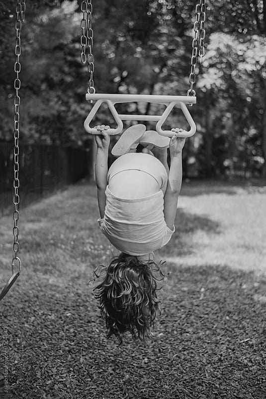 Young girl hanging upside down from a swing by Jakob for Stocksy United