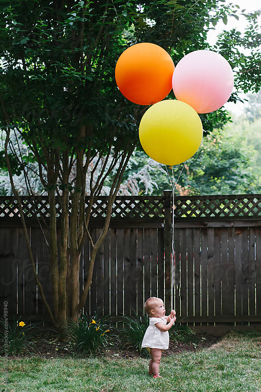 little girl holding giant balloons on her first birthday by Meaghan Curry for Stocksy United