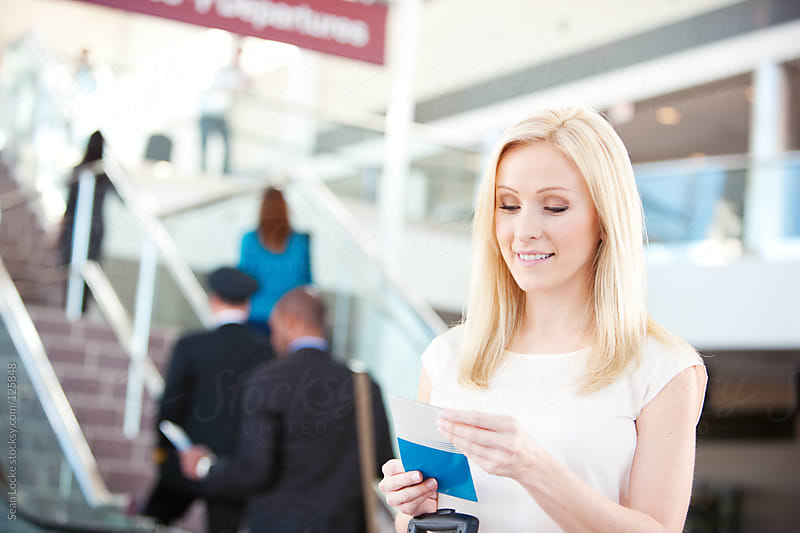Airport: Pretty Woman Checks Ticket Information by Sean Locke for Stocksy United