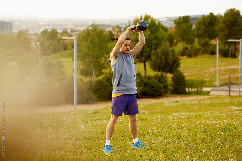 Determined Athlete Lifting Kettlebell In Park by ALTO IMAGES for Stocksy United