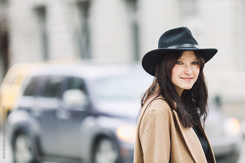 A pretty young woman smiling at an intersection by Ania Boniecka for Stocksy United