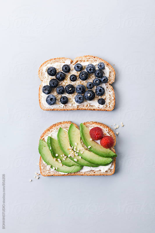 Avocado, blueberries, raspberries and cream cheese on toasts. by BONNINSTUDIO for Stocksy United