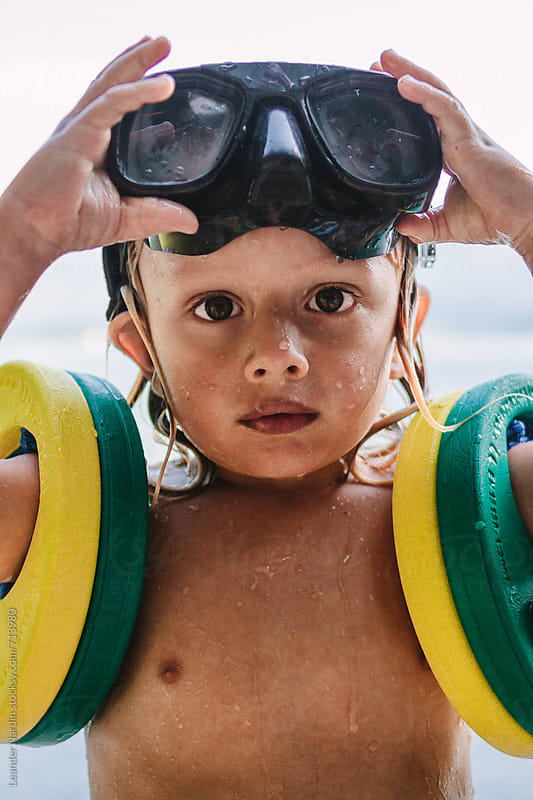 portrait of a wet toddler with diving goggles on the head and swimming rings by Leander Nardin for Stocksy United