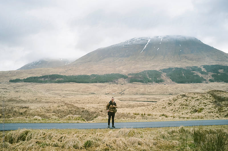 A happy hiker or walker standing on a road surrounded by mountains in the Scottish Highlands by Ivo de Bruijn for Stocksy United