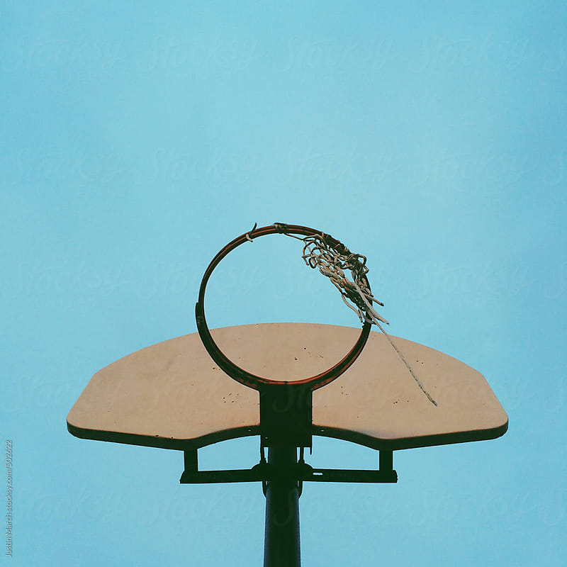 Basketball hoop with a torn net against a bright blue backdrop by Justin March for Stocksy United