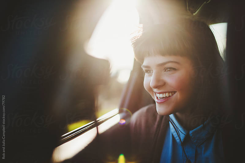 Beautiful teen girl enjoying car ride by Rob and Julia Campbell for Stocksy United