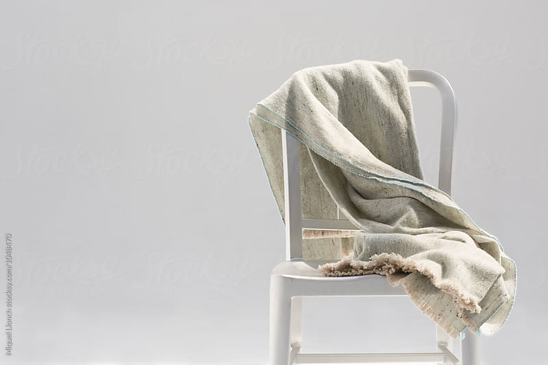 Handmade wool and bamboo blanket on a metallic chair by Miquel Llonch for Stocksy United