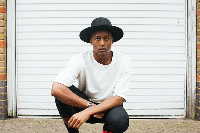 London Street Style - Outdoor Portrait of Young Cool Black Man Crouching in Front of White Garage Door by Julien L. Balmer for Stocksy United