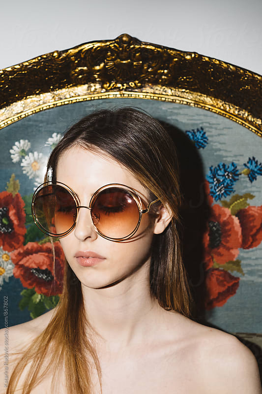Pretty Young Woman With Sunglasses Posing In Front of the Needlepoint    by Katarina Radovic for Stocksy United